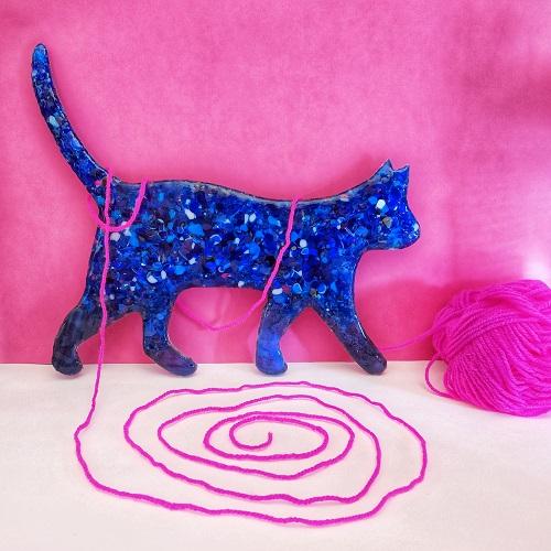 Photo de Chat en verre bleu tacheté de blanc avec une pelote de laine