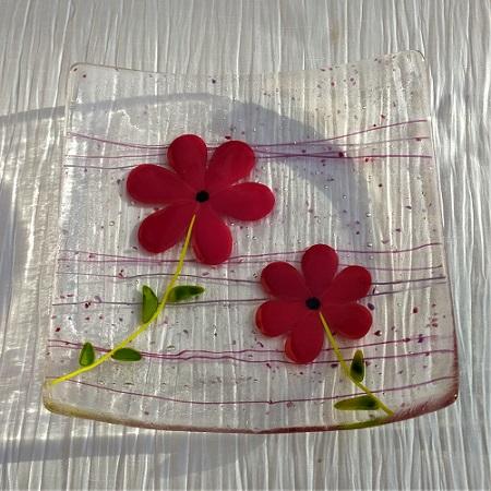 Plat en verre avec deux fleurs rouges