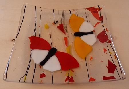 Plat en verre avec deux papillons rouges et orange